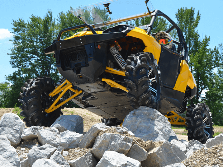 Can-Am Commander with high clearance A-arms installed climbing rocks.