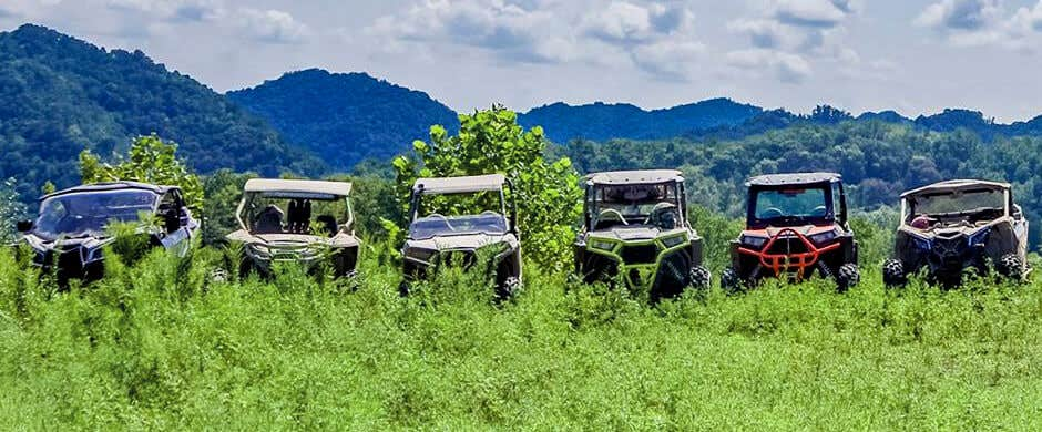 Six UTVs in the grass with mountains in the background.
