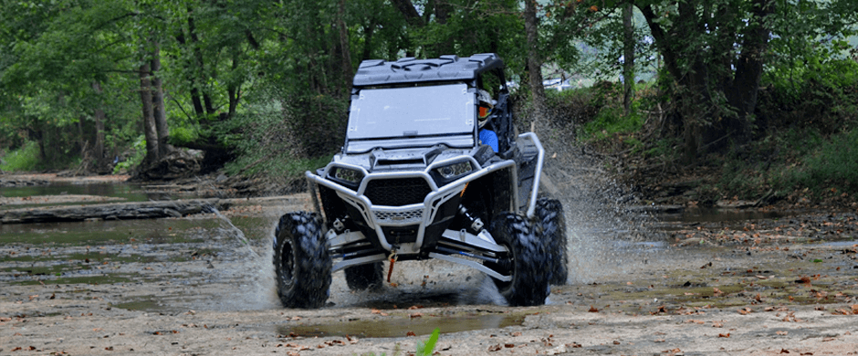 Black Polaris RZR driving through a creek