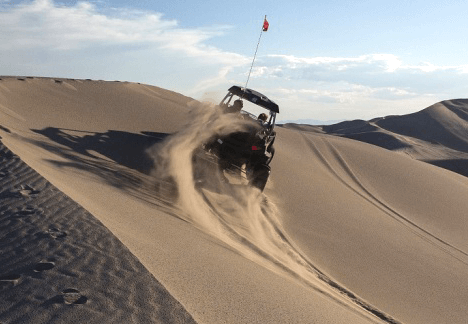 A UTV driving performing a proper transition to get to the other side of the dune.