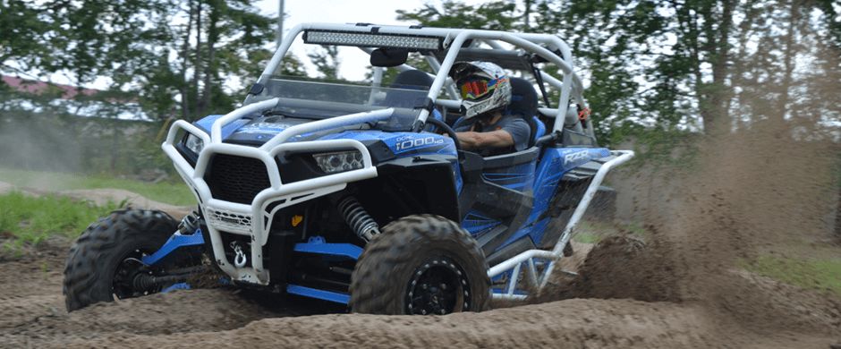 White and blue Polaris RZR 1000 on the track.