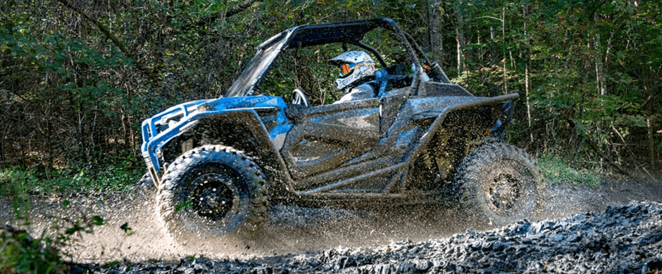 Image of a Polaris RZR tearing through the mud.