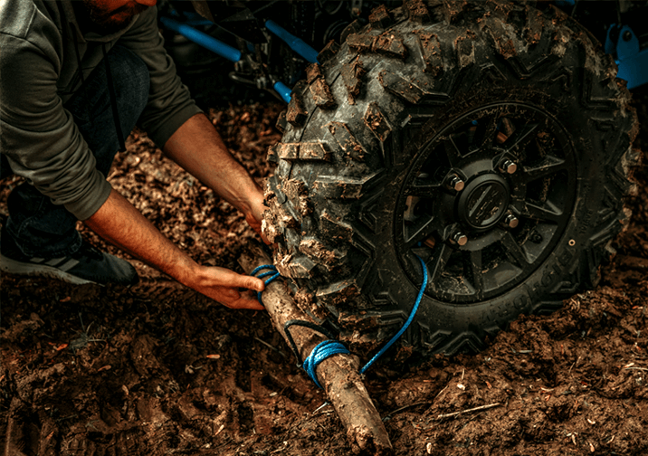 Placing a tree branch under the tire of a UTV stuck in the mud
