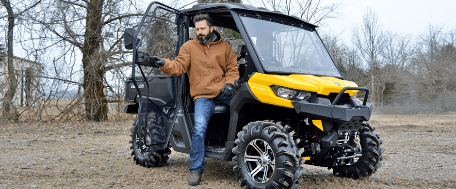 Man Getting Out of Passenger Side Door of a Yellow and Black Can-Am Defender